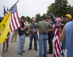 Protestors, some exercising their open-carry rights, assemble outside of the the Wolverine Center in Vassar, Mich., Monday July 14, 2014. They oppose the housing of detained immigrant children at the facility. The immigration issue has pit the Republican Party's Wall Street-friendly leadership against grassroots activists, who are dead-set against any immigration reform that offers a form of amnesty to illegal migrants. THE CANADIAN PRESS/AP-The Saginaw News-Coty Giannelli