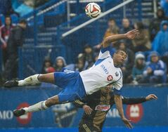 Montreal Impact's Matteo Ferrari, top, collides with Philadelphia Union's Andrew Wenger during second half MLS soccer action in Montreal, Saturday, April 26, 2014. THE CANADIAN PRESS/Graham Hughes