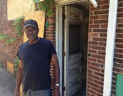 Anthony Brown, 59, stands next to a vacant house adjacent to his home in Detroit's Marygrove neighborhood on Friday, June 13, 2014. Brown hopes that an online auction of city-owned homes helps strengthen his neighborhood and other parts of Detroit. A study prepared for a city blight task force recommends that more than 38,000 houses should be torn down in Detroit. Another 35,000 are unoccupied, abandoned or government-owned and at-risk of becoming blighted. About 5,500 of those are owned by the city or the Detroit Land Bank Authority. (AP Photo/Corey Williams)