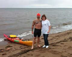 Jeremy Davidson, 32, poses for a photo with Bev Grasse, regional manager with the Neil Squire Society, before starting his swim from Cape Jourimain, N.B. on Saturday Aug.23, 2014. Davidson, 32, arrived back in New Brunswick on Saturday night after spending 16 hours and 15 minutes in the water crossing the Northumberland Strait both ways. THE CANADIAN PRESS/HO-Neil Squire Society