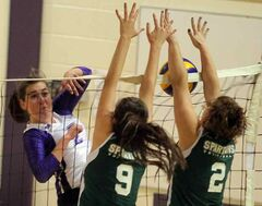 Massey's Carmen Hutsal hammers the ball at Neelin's Alison Quiring (middle) and Tara van den Ham Tuesday.