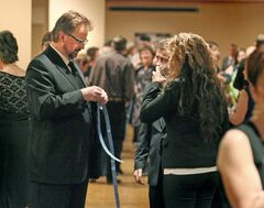 The Brandon Sun managing editor pulls apart a double arms length of raffle draw tickets at the Provincial Exhibition of Manitoba's President's Dinner on Thursday while speaking with CKLQ/STAR FM news director Clay Young and local musician Mariah Phillips of Misty Street.