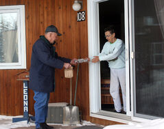 Jack Gullett delivers a hot meal to Leona Kowaluk on Tuesday.