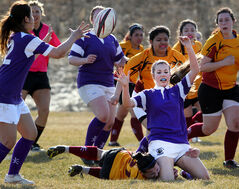 Victoria Rust passes the ball to a Vincent Massey teammate as she crashes to the ground from a tackle during a high school rugby match with Crocus Plains at John Reilly Field on Tuesday afternoon.