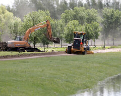 Crews from the RM of Cornwallis construct a permanent dike near Veterans Way on Thursday to protect a nearby strawberry farm and evergreen nursery that were destroyed in the 2011 flood.