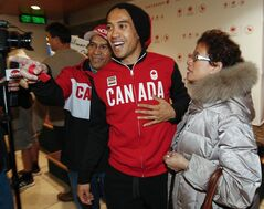 Long track speedskater Gilmore Junio, centre, stands with his parents, Gino Junio, left, and Julie Junio after arriving home from the Sochi Olympics in Calgary, Alta., Tuesday, Feb. 25, 2014.THE CANADIAN PRESS/Jeff McIntosh