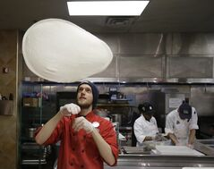 In this Thursday, March 27, 2014 photo, John Pittenger tosses up a pizza dough at the Whole Foods Market in Woodmere Village, Ohio. The Labor Department releases its May report on producer prices on Friday, June 13, 2014. (AP Photo/Tony Dejak)