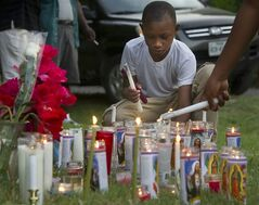 Darrel Brown, 8, lights candles at a makeshift memorial for Pearlie Golden during a vigil at Golden's home Wednesday, May 7, 2014, in Hearne, Texas. Golden was shot and killed outside her home by a Hearne police officer on Tuesday after she allegedly brandished a firearm the Hearne Police Department said. (AP Photo/Bryan-College Station Eagle, Stuart Villanueva)