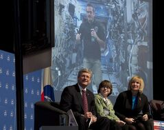 Robbie Passmore Waugh sits with Canadian Prime Minister Stephen Harper and Laureen Harper as the Prime Minister asks Commander of the International Space Station Chris Hadfield a question via video conference Friday March 15, 2013 in Ottawa. THE CANADIAN PRESS/Adrian Wyld