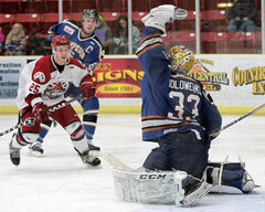 Swan Valley Stampeders goalie Cole Holowenko makes a glove save as teammate Evan Morden and Curtis Oliver of the Virden Oil Capitals look on during Saturday night's MJHL playoff game.