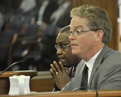 Rep. Thomas Stallworth III, left, D-Detroit, left, assumes a prayerful position while colleague Rep. John Walsh, R-Livonia speaks tothe senate committee on Government Operations on the bills associated with easing Detroit's bankruptcy in Lansing, Mich., Tuesday, June 3, 2014. Michigan's Senate approved on Tuesday spending $195 million to help prevent steeper cuts in Detroit retiree pensions, linking the state with a deal designed to shield valuable city-owned art from being sold and resolve the largest public bankruptcy in U.S. history. The (AP Photo/Detroit News, Dale G. Young) DETROIT FREE PRESS OUT; HUFFINGTON POST OUT. MANDATORY CREDIT