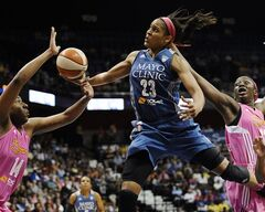 FILE - In this July 27, 2014, file photo, Minnesota Lynx's Maya Moore, center, glides to the basket as Connecticut Sun's Kelsey Bone, left, and Chiney Ogwumike, right, defend during the second half of a WNBA basketball game in Uncasville, Conn. Moore has won the WNBA most valuable player award, a person close to the situation told The Associated Press on Wednesday night, Aug. 20, 2014. Moore will receive the award Thursday night in Minnesota before the Lynx face San Antonio in the first game of the Western Conference semifinals. (AP Photo/Jessica Hill, File)