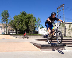 Zack Hodgsen, 10, takes a jump on his BMX bike at the Kristopher Campbell Memorial Skate Plaza on Friday afternoon, as his friend Zach Gwyer, 12, circles around to take a turn behind. The skateboard park was designed right from its first designs to echo the Prince Edward Hotel.