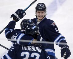 Winnipeg Jets' Jacob Trouba (8), Mark Stuart (5) and Chris Thorburn (22) celebrate Thorburn's goal during first period NHL hockey action against the Nashville Predators in Winnipeg, Tuesday, January 28, 2014. Trouba turned 20 on Wednesday, but the Jets defenceman is hoping for a belated birthday gift about six weeks from now.That present would be a spot in the NHL playoffs to cap off his strong rookie season.THE CANADIAN PRESS/Trevor Hagan