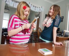 Ten-year-old Mei Thiessen and her 13-year-old sister Ruth play a board game during a learning exercise earlier this week. Mei, Ruth and their older sister Kate have been home schooled by their mother Jolene for the majority of their grade school years at their home in Oak Lake.