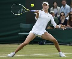 Eugenie Bouchard of Canada plays a return to Andrea Petkovic of Germany during their women's singles match at the All England Lawn Tennis Championships in Wimbledon, London, Saturday, June 28, 2014. (AP Photo/Alastair Grant)