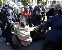 Montenegro police officers arrest demonstrators during a protest in Podgorica, Montenegro, Saturday, Feb. 15, 2014. The demonstrators who assembled in the downtown area of the capital, Podgorica, on Saturday demanded the resignation of the government of the long-standing prime minister, Milo Djukanovic. They accuse his government of rampant corruption, unemployment and economic mismanagement. (AP Photo/Darko Vojinovic)