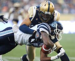 Winnipeg Blue Bombers' Graig Newman (3) tackles Toronto Argonauts' Terrell Sinkfield (83) during the first half of preseason CFL football action at Investors Group Field in Winnipeg, Monday, June 9, 2014. Newman will miss the entire regular season after suffering a serious ankle injury in a pre-season game over the weekend. THE CANADIAN PRESS/Trevor Hagan