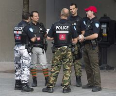 Montreal Police officers are shown on a street in Montreal, Thursday, August 7, 2014. The funky pants and sticker-plastered city vehicles are just the beginning as workers and the province draw battle lines over a proposed reform of municipal pensions. THE CANADIAN PRESS/Graham Hughes