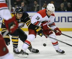 Buffalo Sabres' Cody McCormick (8) battles for the puck with Carolina Hurricanes' John-Michael Liles (26) during the first period of an NHL hockey game in Buffalo, N.Y., Tuesday, Feb. 25, 2014. (AP Photo/Gary Wiepert)