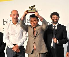 FILE - In this Saturday, June 7, 2014 file photo, Korean Pavilion curator Minsuk Cho holds up the Golden Lion award for the Best National Participation during the award ceremony of the 14th International Architecture Exhibition of the Venice Biennale, in Venice, Italy. At left is Biennale President Paolo Baratta, and at right, Italian Culture Minister Dario Franceschini. The Korean Pavilion, which included material from both North and South Korea for the first time, won the Golden Lion for best national pavilion. (AP Photo/Luigi Costantini, file)