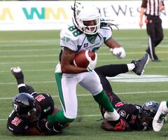 Saskatchewan Roughriders' Taj Smith(88) has his feet grabbed by Ottawa Redblacks' Jasper Simmons (31) Jarrel Williams (24) during CFL football action in Ottawa, Saturday August 2, 2014. THE CANADIAN PRESS/Fred Chartrand