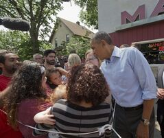 President Barack Obama greets a small child on the sidewalk outside of Matt's Bar in Minneapolis, Thursday, June 26, 2014, after having lunch with Rebekah Erler. Obama traveled to Minnesota to begin a two-day trip, where he plans to put a human face on the economic policies he and Democrats are championing, and met with Erler, who wrote the White House about her struggles to make ends meet. (AP Photo/Pablo Martinez Monsivais)