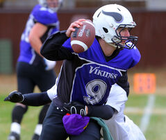 Vikings' QB Evan Didychuk looks for an opening while being tackled Friday.