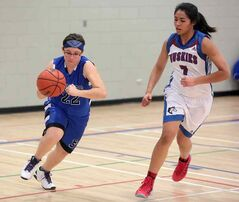 Souris's Charlotte West drives past Sturgeon Heights' Jess Ahmed.