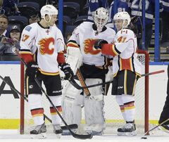 Calgary Flames goalie Karri Ramo, of Finland, center, celebrates with teammate Lance Bouma, left, and Chad Billins, right, after they defeated the Tampa Bay Lightning 4-1 during an NHL hockey game on Thursday, April 3, 2014, in Tampa, Fla. The Flames have made qualifying offers to six of their restricted free agents, including Bouma and Billins. THE CANADIAN PRESS/AP/Chris O'Meara