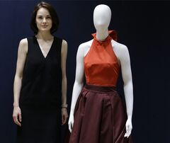 RECROP OF LKW106 In this Wednesday, May 14, 2014 photo, British actress Michelle Dockery, stands with her Prada gown that she wore to the 2013 Emmy's, at Christie's auction rooms in London.