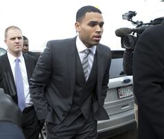 FILE - In this Jan. 8, 2014, file photo, singer Chris Brown, right, arrives at the District of Columbia Superior Court in Washington, for a status hearing in a case in which he's accused of hitting a man outside a Washington hotel. He didn't fly first class and his hotels weren't five-star. Still, when Brown was moved from a Los Angeles jail to Washington for what was to have been the start of his trial on an assault charge, the cost to taxpayers was more than $4,000. The breakdown of the April trip was provided to The Associated Press as a result of a Freedom of Information Act request. (AP Photo/Manuel Balce Ceneta, File)