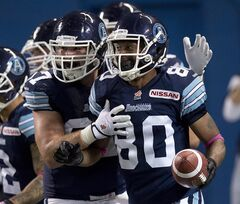 Toronto Argonauts wide receiver Romby Bryant (80) is congratulated by teammate Jeff Keeping (67) after hauling in a touchdown pass against the Winnipeg Blue Bombers during first half CFL action in Toronto on Thursday Oct. 24, 2013. Bryant admits he wondered whether his career had come to an end when he was cut by the Argonauts. THE CANADIAN PRESS/Frank Gunn