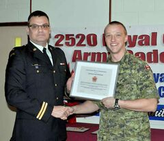 Capt. Rob Lussier presents Lt. Dane Nickolson of the CFB Shilo Military Police with the CO's Commendation plaque.