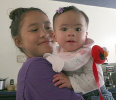Zachi Espayos smiles as she holds her sister Zoey at Mom's Kitchen in Hamiota on Thursday.