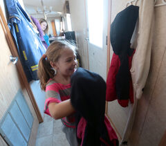 Abby Leslie hangs up her jacket after school on Tuesday at her home in the Glendale Mobile Home Park as mom Robin Leslie looks on.