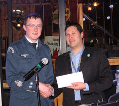 Warrant Officer Eric Church presents a donation from the cadets to club president Nonny Cancade for the Rotary Westman Foundation.