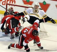 Boston Bruins' Milan Lucic (17) collides with Ottawa Senators' Colin Greening (14) during third period NHL hockey action in Ottawa on Saturday, December 28, 2013. The Senators defeated the Bruins 4-3. THE CANADIAN PRESS/Fred Chartrand