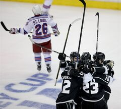 Members of the Los Angeles Kings celebrate Dustin Brow's goal as New York Rangers right wing Martin St. Louis skates off during the second overtime period in Game 2 in the NHL hockey Stanley Cup Finals in Los Angeles, Saturday, June 7, 2014. (AP Photo/Jae C. Hong)