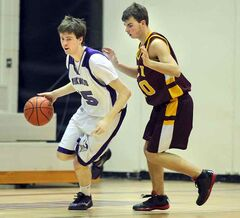 Vincent Massey Vikings' Iain Cowie drives past Portage Tigers' Chaz Brown in the Triple Crown Zone Challenge.