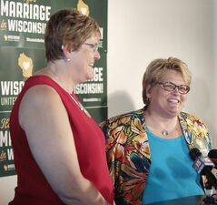 Katy Heyning, left, and Judi Trampf, right, plaintiffs in Wolf v. Walker, speak during a press conference at Plan B in Madison, Wis., Thursday, Sept. 4, 2014. Earlier in the day, the 7th Circuit Court of Appeals in Chicago struck down the gay marriage bans of Wisconsin and Indiana as unconstitutional. (AP Photo/Wisconsin State Journal, M.P. King)
