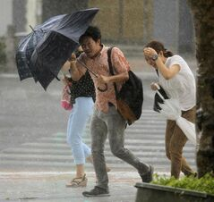 People hold umbrellas through heavy rain caused by a typhoon in Naha, Okinawa, Wednesday, July 9, 2014. A powerful storm slammed through the southwestern Japanese island of Okinawa, leaving at least 28 people injured and 63,000 homes without power before swerving toward the bigger island of Kyushu on Wednesday. (AP Photo/Kyodo News) JAPAN OUT, MANDATORY CREDIT