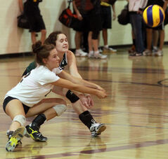 Neelin's Tara van den Ham, left, and Jordan Hardy collide with one another while digging up a serve from the Crocus Plainsmen during Tuesday's high school volleyball match.