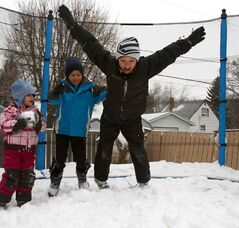 Cayden Glover dives in a pile of snow on his trampoline on Saturday as Calder Crossin and Devin Kerman-Forsythe look on.