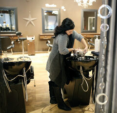 Straight Up Salon hairstylist Nicole Avery washes Nearly New Shop volunteer co-ordinator Enid Graham's hair.