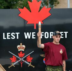 A soldier from CFB Shilo hold the baton high in front of a statue that reads: