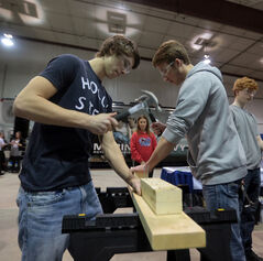 Shoal Lake students Dylan Kimpinski, left, and James Sytnyk race to drive in nails at an apprenticeship booth during the symposium on Tuesday.