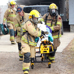 Brandon Fire and Emergency Services members wheel an 84-year-old woman to a waiting ambulance at the scene of a house fire at      30 Balmoral Bay in the city's south end early Sunday afternoon. Police said the woman was transported to hospital, where she was pronounced dead. Another resident of the home was out at the time of the blaze and was not injured.