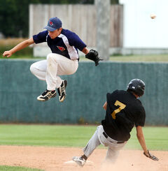 Dustin Asham of the Canadian Tire Cardinals leaps to try to catch the throw to second as Jordan Old of the Joe Beeverz Young Guns slides safely into the bag during the first game of the Andrew Agencies Senior AA Baseball League final Wednesday evening at Andrews Field.