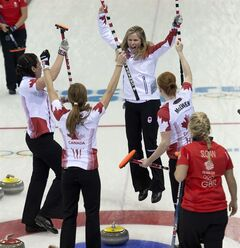 Team Canada skip Jennifer Jones jumps for joy and celebrates with teammates Jill Officer(left), Kaitlyn Lawes and Dawn McEwen(right) as Great Britain's Anna Sloan looks at the final stone of the 10th end during semi-final curling action at the Sochi Winter Olympics Wednesday February 19, 2014 in Sochi, Russia. Canada defeated Great Britain 6-4 to advance. THE CANADIAN PRESS/Adrian Wyld